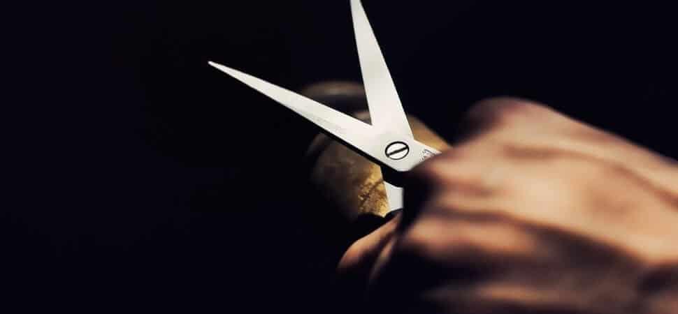 Een hand met een schaar als metafoor voor cost cutting versus Lean management